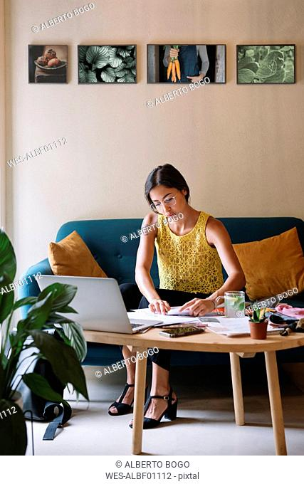 Fashion designer sitting on couch working on a new collection