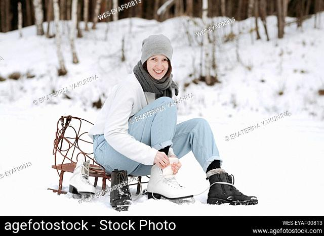 Portrait of smiling woman putting on ice skates on snow field