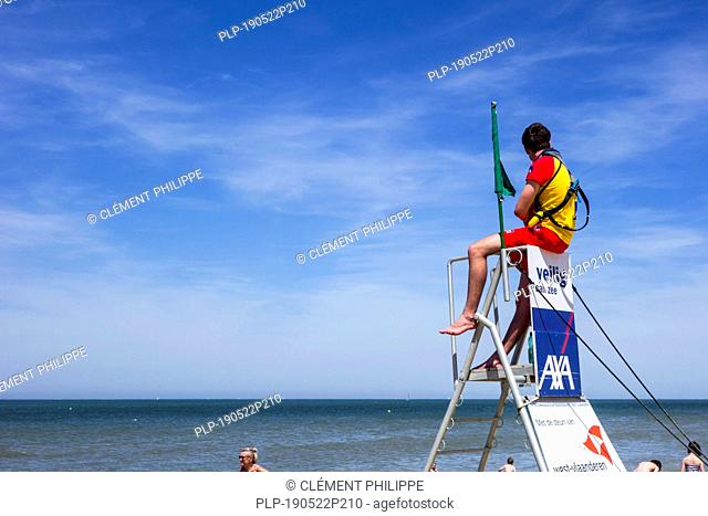 Beach lifeguard supervising bathers and swimmers along the Belgian North Sea coast from portable high chair / tower, Belgium