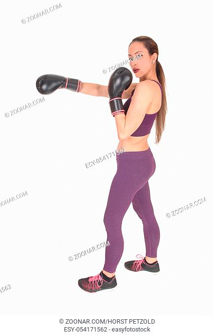 A full body image of a woman boxing and in workout outfits standing isolated for white background