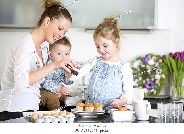 Mother and family with cupcakes in kitchen
