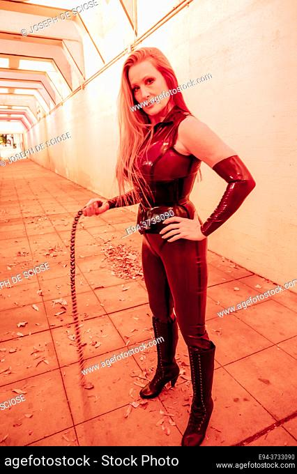 A beautiful 51 year old tall blond dominatrix woman dressed a latex costume, holding a whip in a lighted underpass