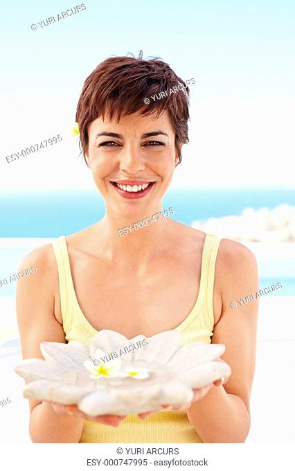 Sweet young woman holding a flower replica, outdoors