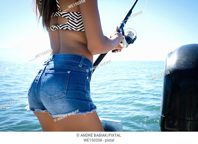 Close up section of female body holding fishing pole - young woman fishing from boat