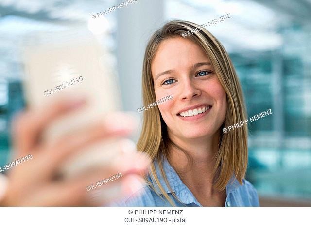 Young businesswoman taking smartphone selfie