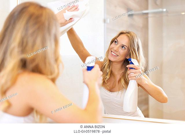 Young blonde woman cleaning mirror in bathroom. Debica, Poland