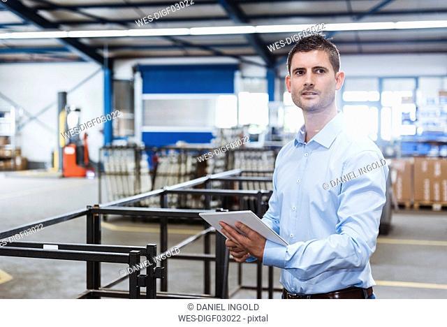 Young man working in shop floor, using digital tablet