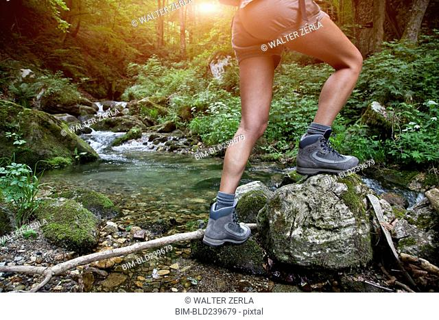 Legs of Caucasian woman hiking over river