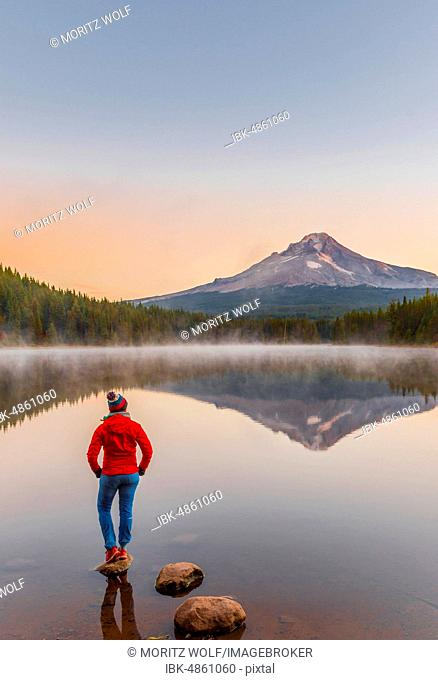 Young woman looking at view of volcano Mt. Hood with reflection in lake Trillium Lake, at sunrise, Oregon, USA