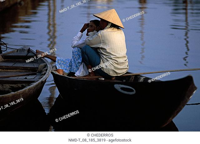 Rear view of a mid adult couple sitting in a boat, Vietnam