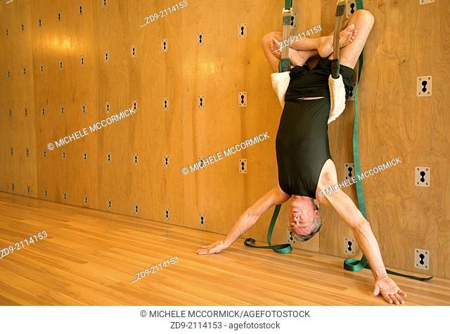 A middle-aged man demonstrates an ashtanga yoga pose on the yoga wall