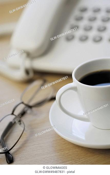 Close-up of eyeglasses and a tea cup in front of a telephone