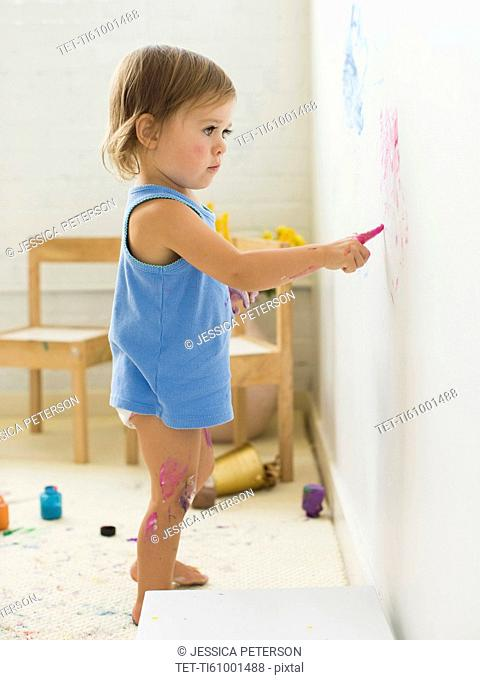 Girl (2-3) painting on wall