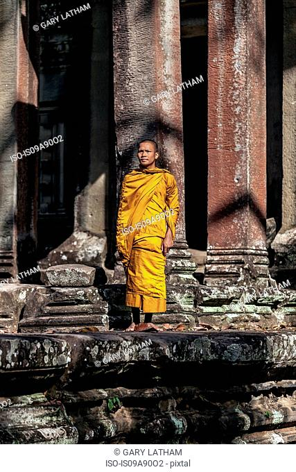 Young Buddhist monk praying outside temple in Angkor Wat, Siem Reap, Cambodia