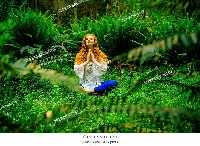 Young woman practicing yoga in lotus position in forest