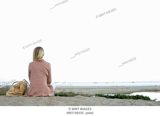 Blond woman sitting on a sandy beach
