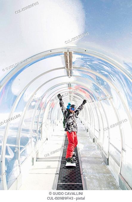 Portrait of snowboarder in ski run tunnel, on moving walkway