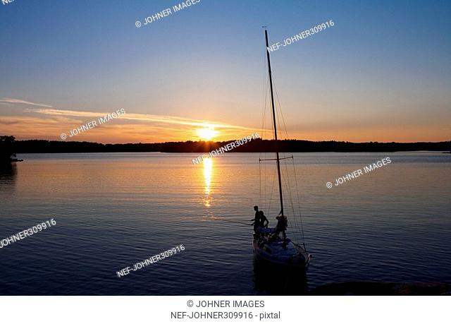 Two men on a sailing boat in the sunset