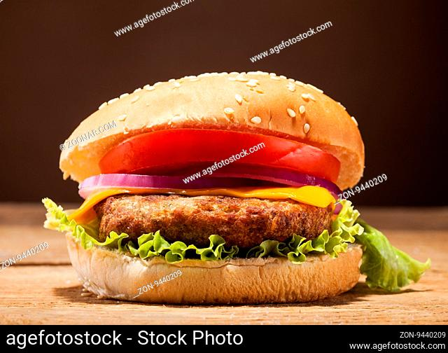 Fresh delicious burger with cheese, tomato, onion and lettuce on wooden table and brown background with copy space