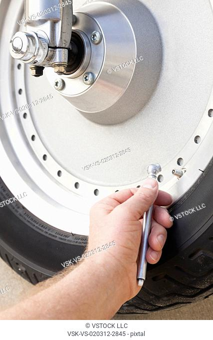 USA, Illinois, Metamora, Close up of man's hand checking pressure in motorcycle tire