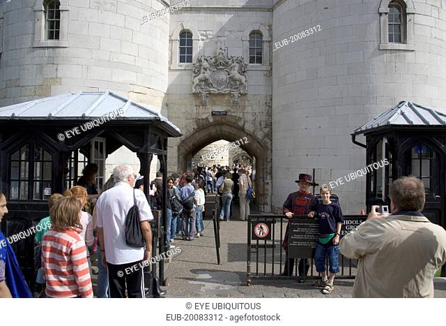 Tourists entering the Tower of London, yoing boy having his picture teken with a Yoeman Warder or Beefeater