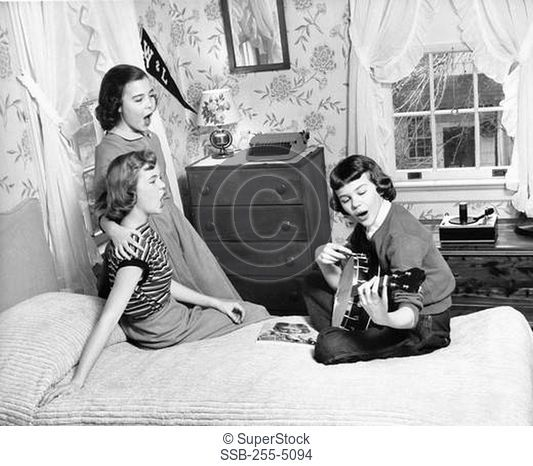 Girl playing a guitar with two girls singing with her