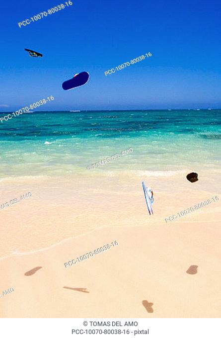Flipflops flying through the air above turquoise ocean and white sand beach