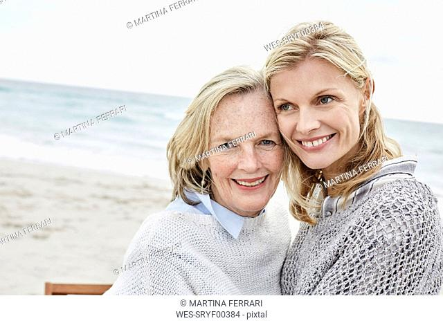 Mother and daughter embracing on the beach