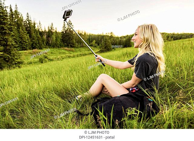A young woman with long blond hair takes a self-portrait with a selfie stick and smart phone while sitting in a grass field in a park; Edmonton, Alberta, Canada