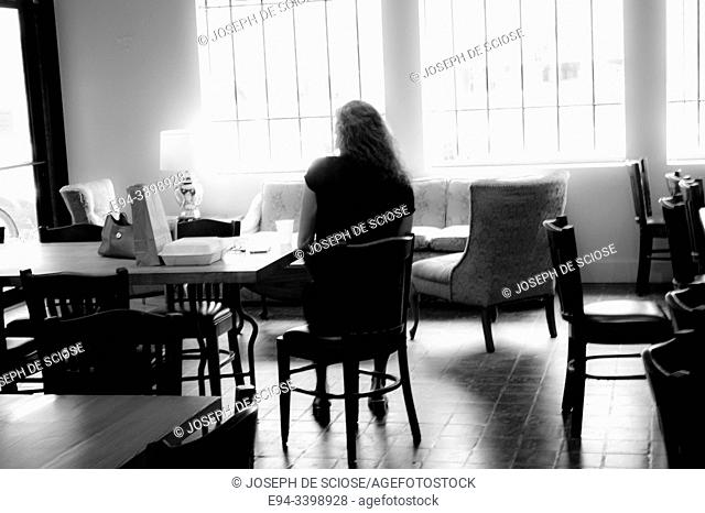 A single woman sitting by herself in a restaurant