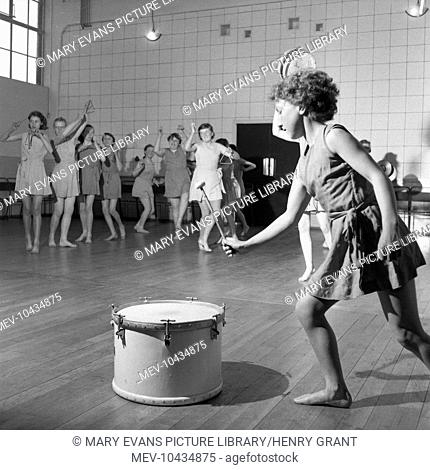 A group of barefooted teenage girls learn to be graceful and lady-like during a lesson of musical movement, which involves playing various musical instruments...