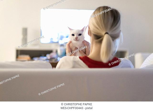 Woman sitting with her cat on the couch watching TV