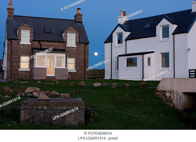 Full moon rising between houses in Kintra harbour