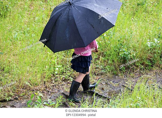 Young girl walking on a muddy trail with rubber boots and an umbrella on a rainy day, Palmer, Southcentral Alaska, summer