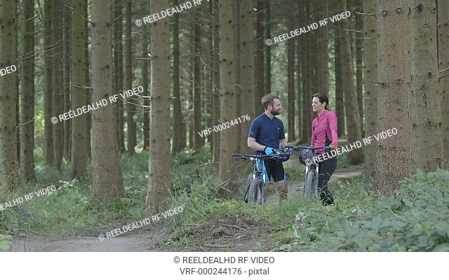 Couple cycling in forest after taking break