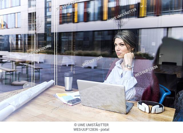 Young woman with laptop and documents behind windowpane
