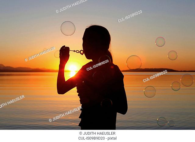 Young girl, outdoors, blowing bubbles, at sunset