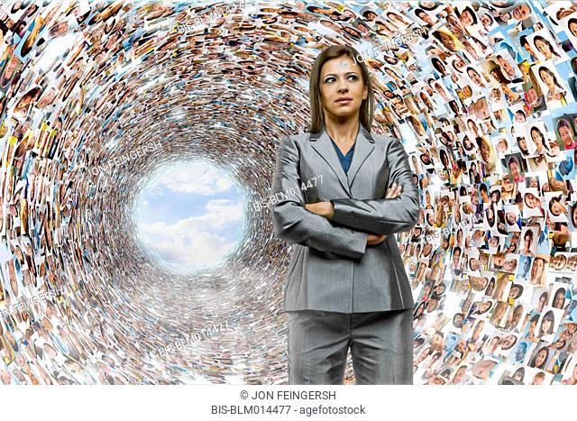 Hispanic businesswoman surrounded by images of business people