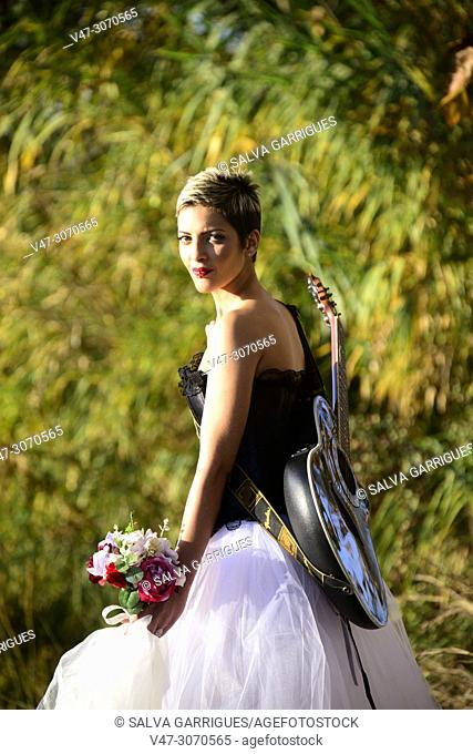 Rock girlfriend with her guitar and her bridal bouquet