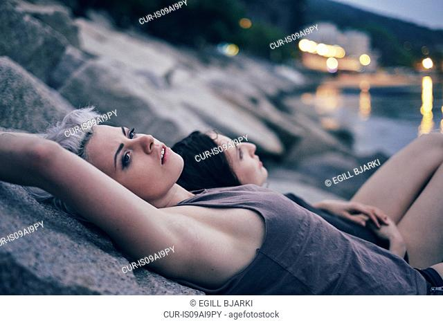 Two young women lying on harbor rocks at dusk
