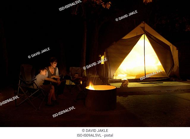 Mature woman and two sons watching campfire at night, County Park, Los Angeles, California, USA