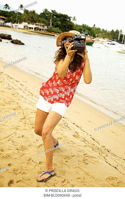 Mixed race woman on beach with camera