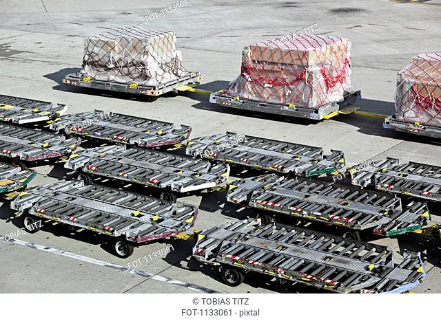 Empty baggage trailers and cargo on an airport tarmac