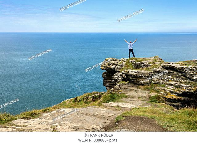 United Kingdom, England, Cornwall, Tintagel, North Coast, Tourist standing on rock