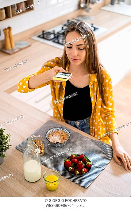 Young woman taking cell phone picture of her breakfast at home
