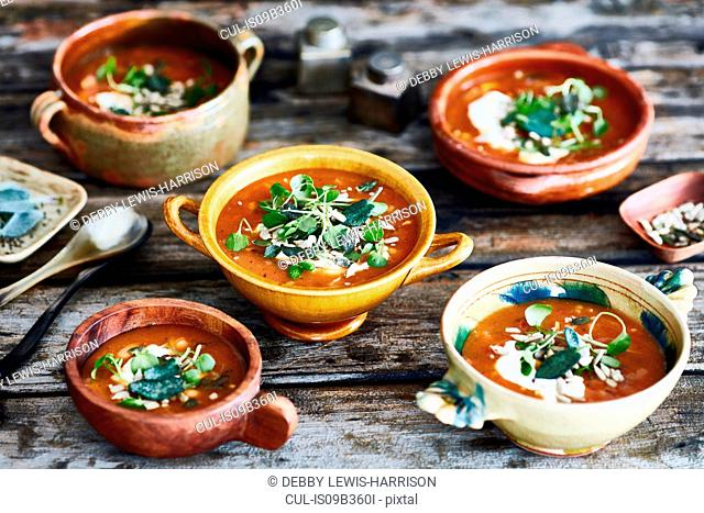 Bowls of garnished soup on wooden table