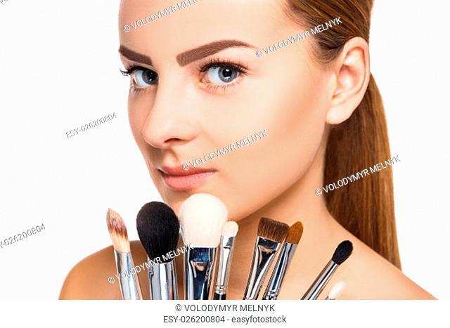 Beautiful female eyes with make-up and brushes on white