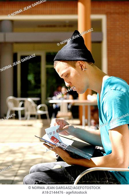 A young man on a college campus looking through educational brochures