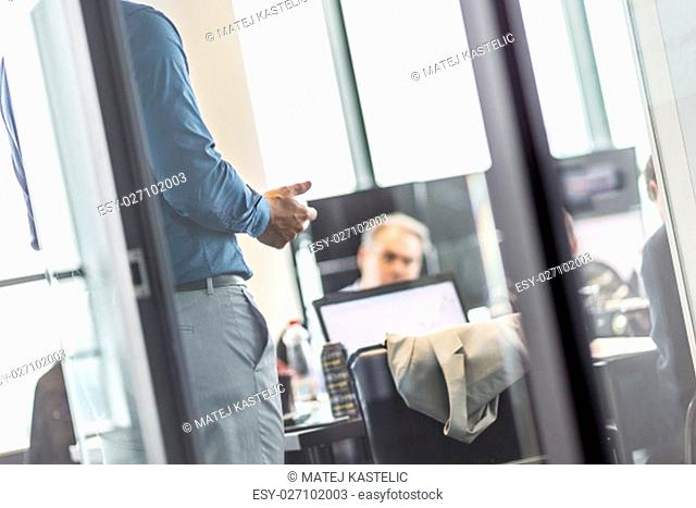 Business man making a presentation at office. Business executive delivering a presentation to his colleagues during meeting or business training
