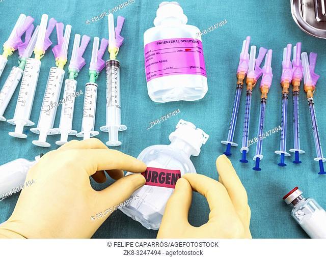 Nurse preparing hospital medication, Pasting urgent label on medication bottle, conceptual image, horizontal composition